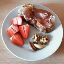 Pão com presunto e queijo, morangos e frutos secos