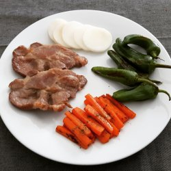 Plumas de porco com pimento padrão e cenouras grelhadas